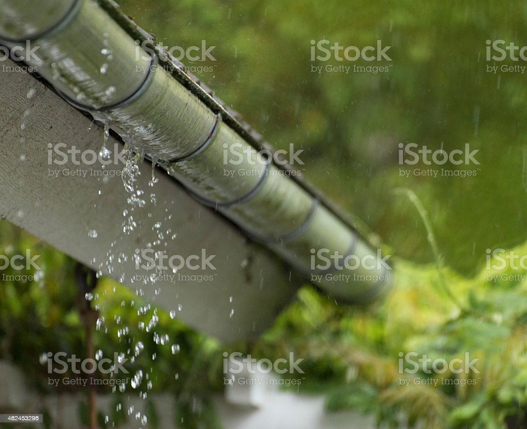 Filled gutter in summer rain stock photo