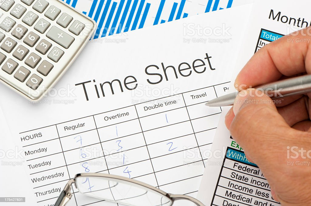 Filled out Time Sheet with writing hand stock photo