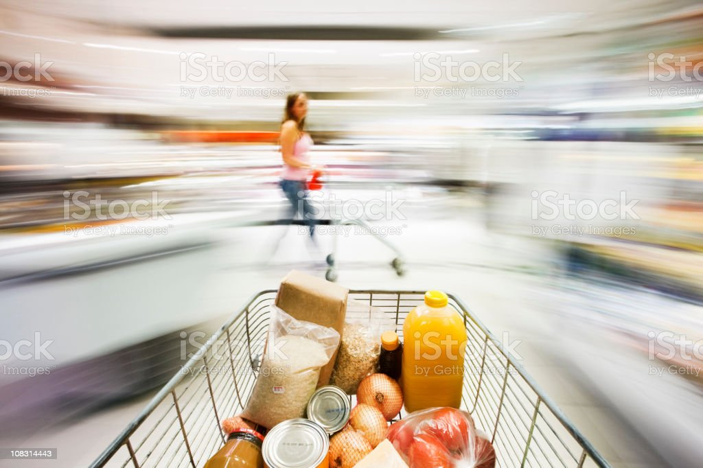 Filled shopping cart races through supermarket in blurred motion royalty-free stock photo