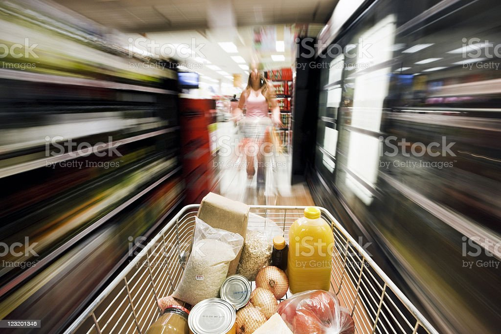 Filled shopping cart rushes down aisle showing exaggerated motion blur royalty-free stock photo