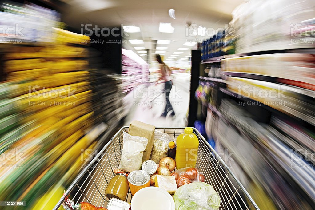 Filled supermarket trolley races down aisle showing extreme motion blur. stock photo