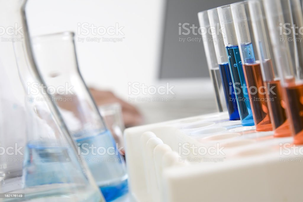 Filled Test Tubes, Beakers, and Chemist Using Computer royalty-free stock photo