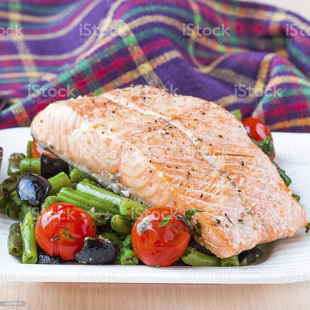 Fillet of fish salmon with green beans, tomatoes and black stock photo