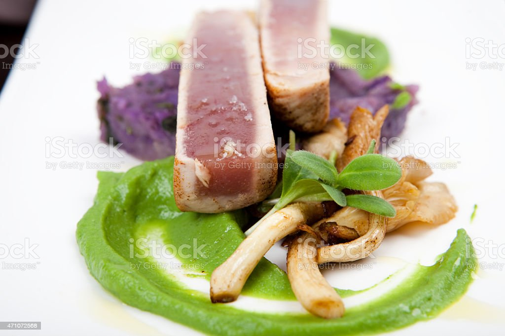 fillet of tuna with oyster mushrooms, pea puree and potatoes stock photo