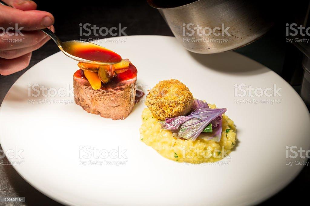 Fillet steak, risotto, braised beef bon bon, carrots & jus stock photo