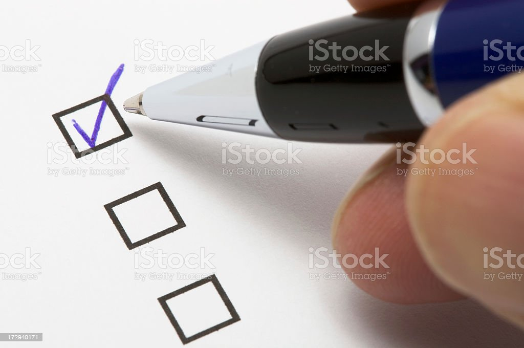 Filling a check box with a blue ballpoint pen royalty-free stock photo