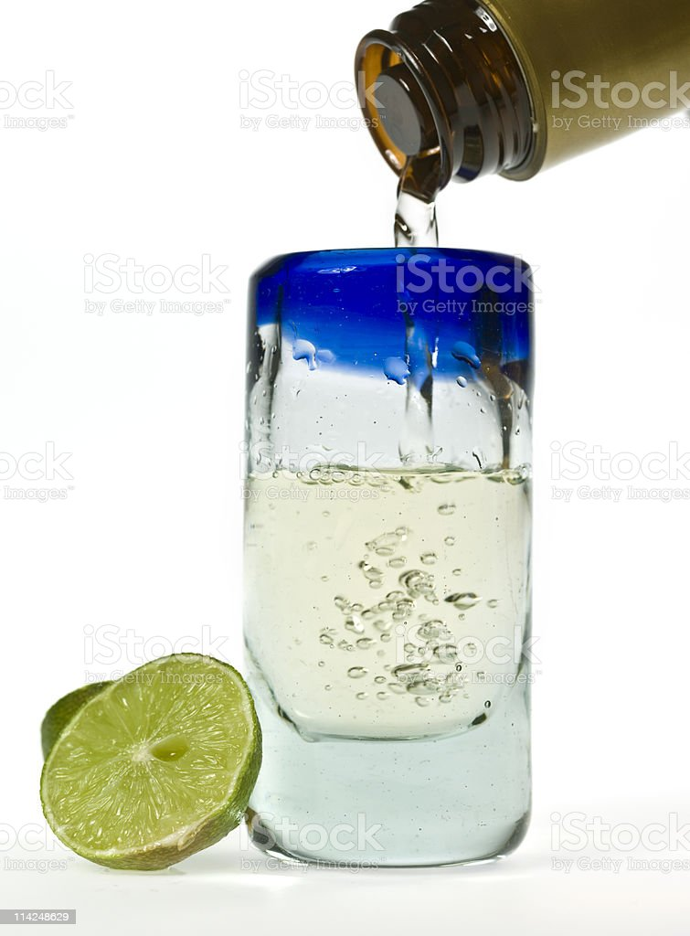 Filling a shoot glass of blue agave tequila stock photo