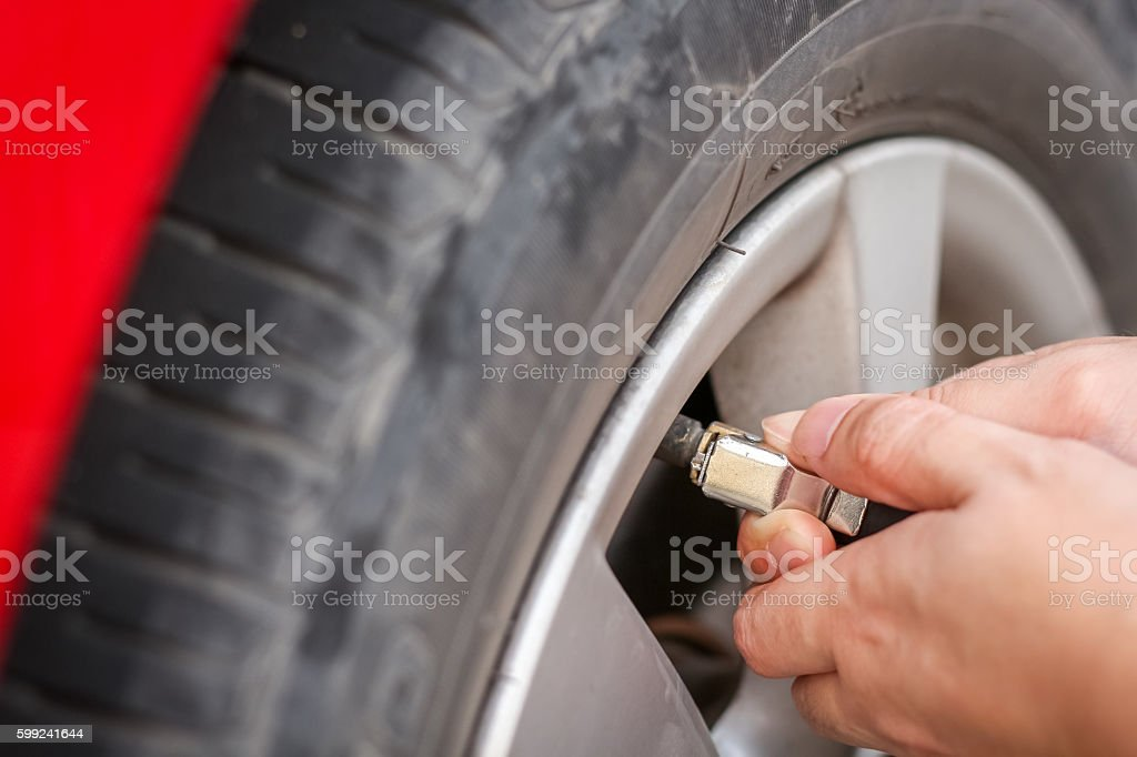 Filling air into a grungy car tire to increase pressure stock photo