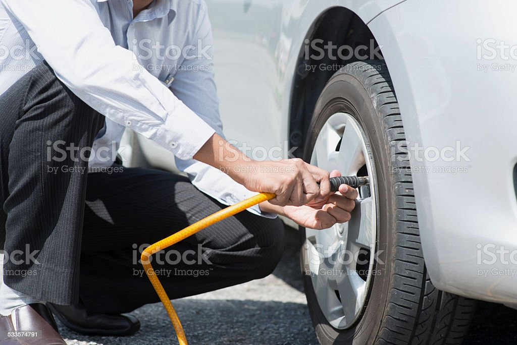 Filling air to the car tires. stock photo