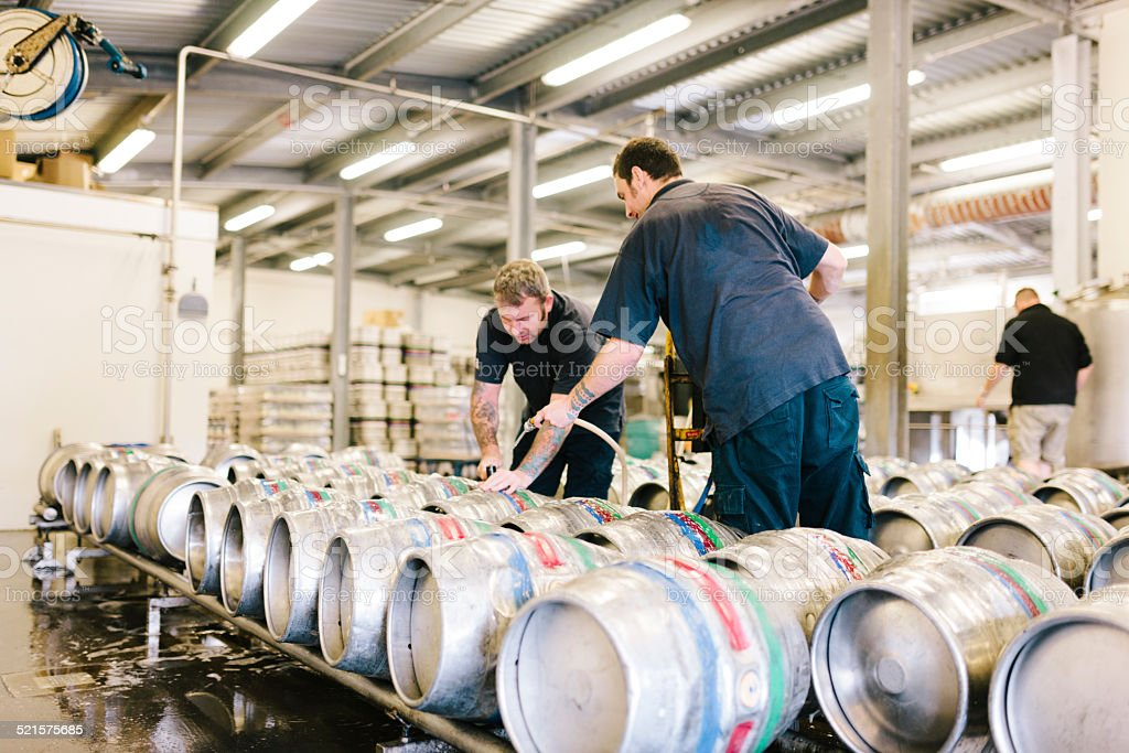 Filling beer kegs with real ale in a brewery warehouse stock photo