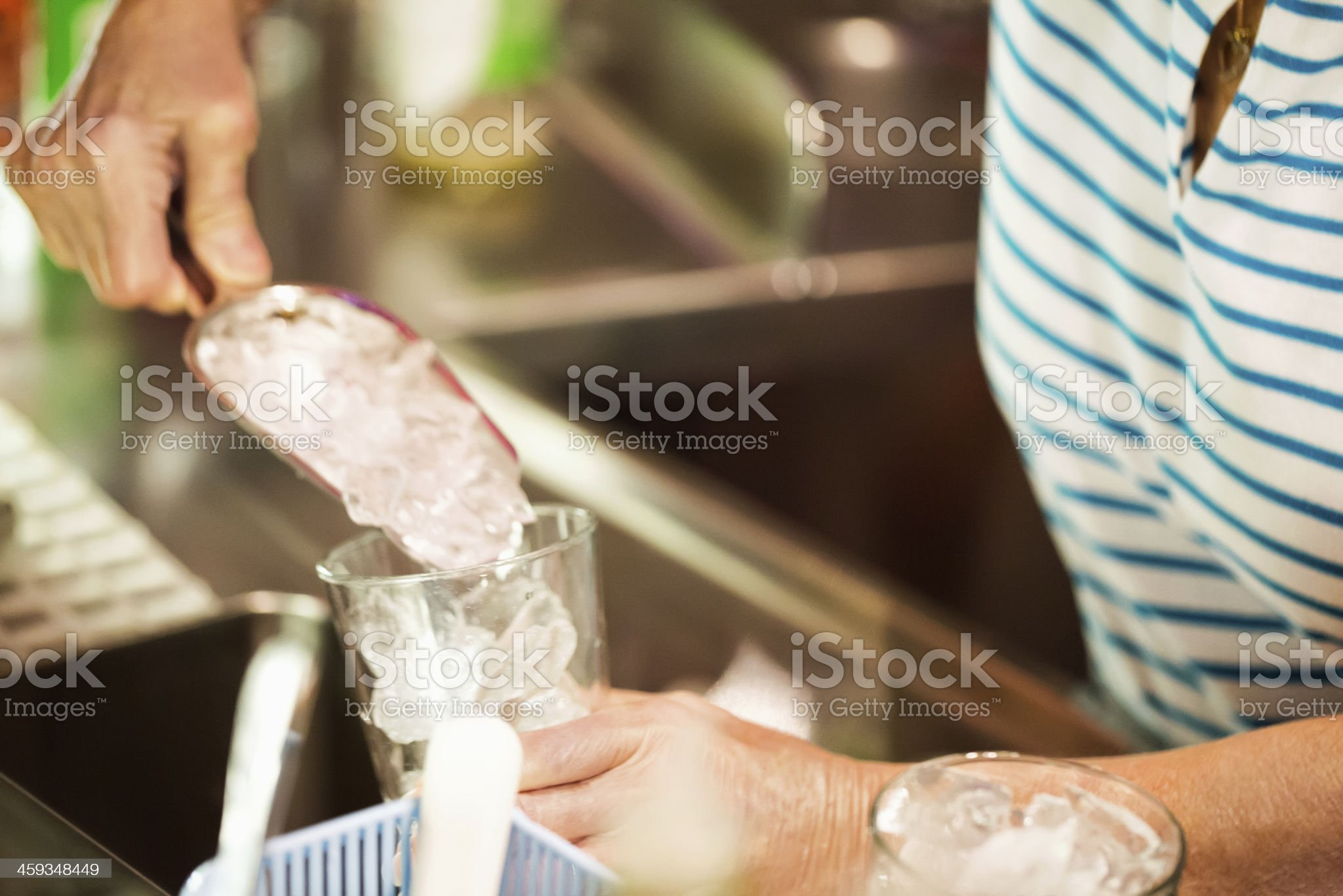 Filling glass with ice from a scoop in bar royalty-free stock photo