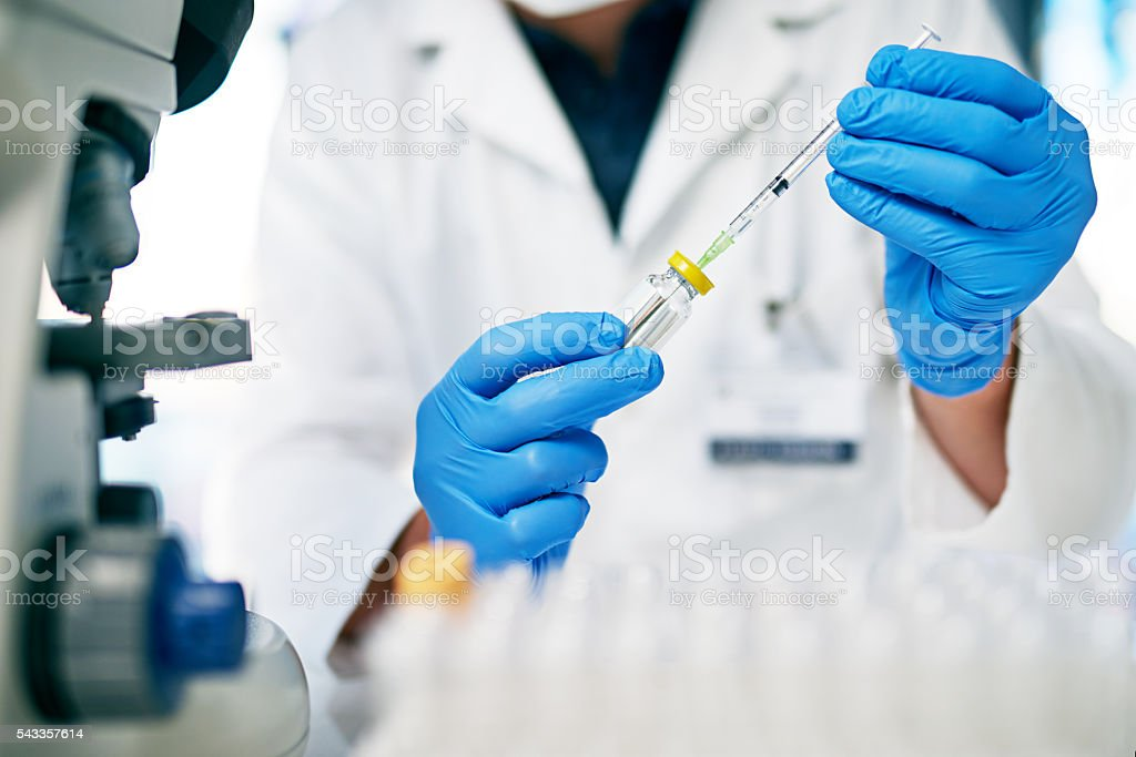 Filling his syringe with what could be a cure... stock photo