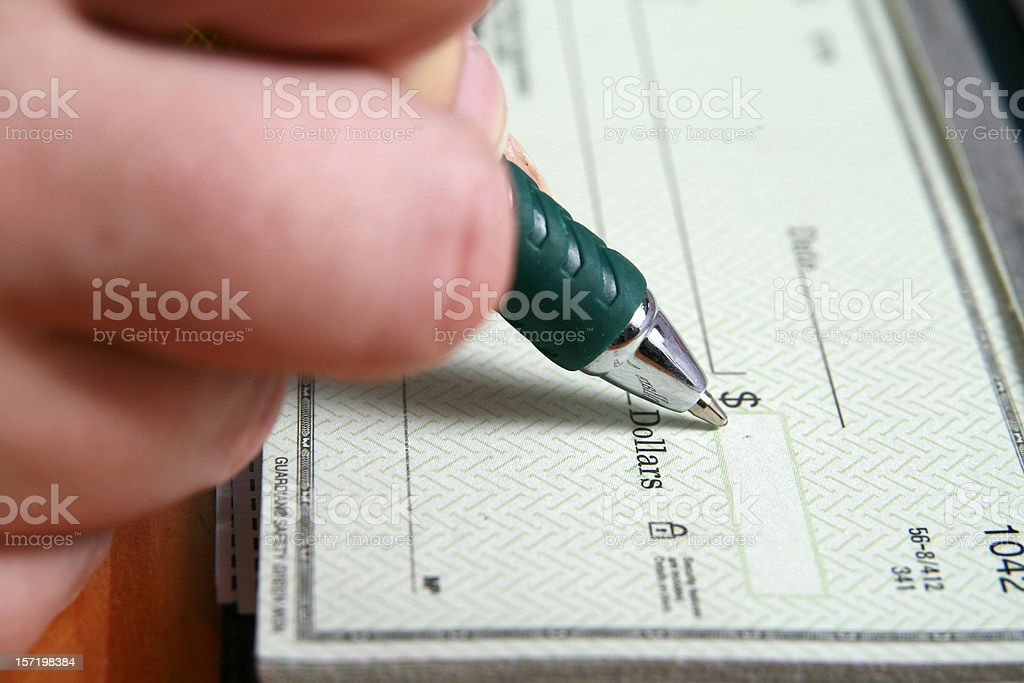 Filling in a blank check with a pen royalty-free stock photo