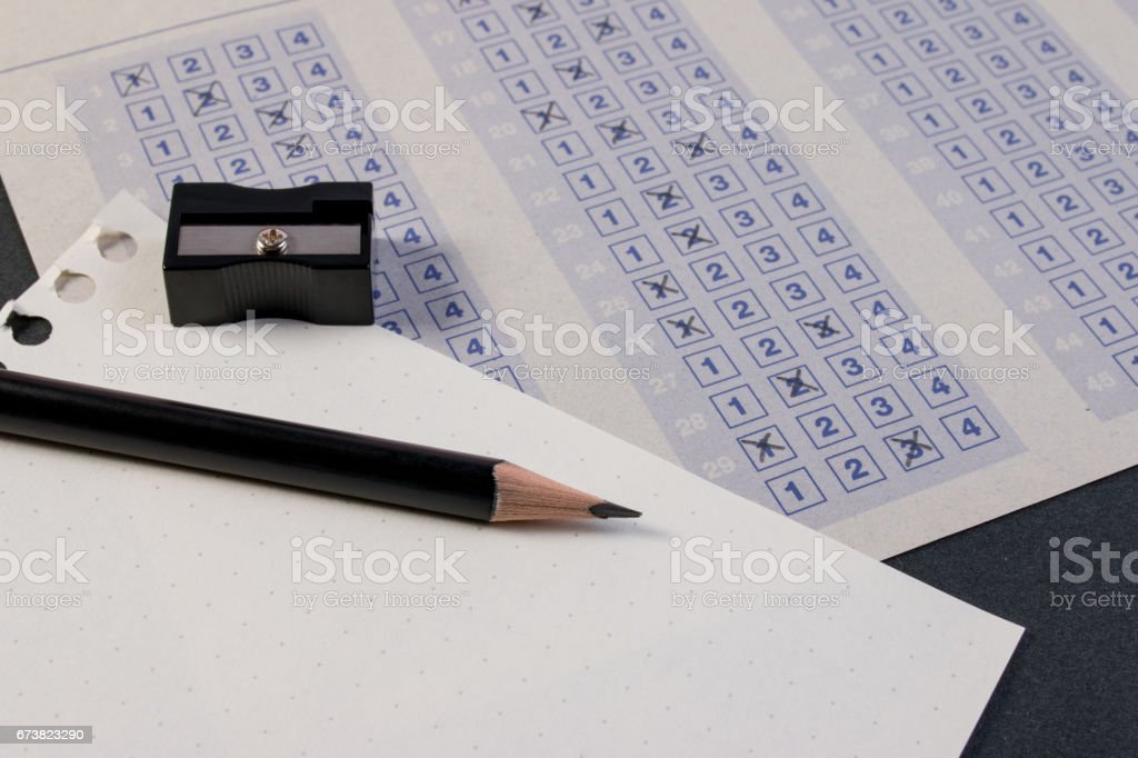 Filling out in answer sheet with pencil, sharpener and paper reduction. stock photo