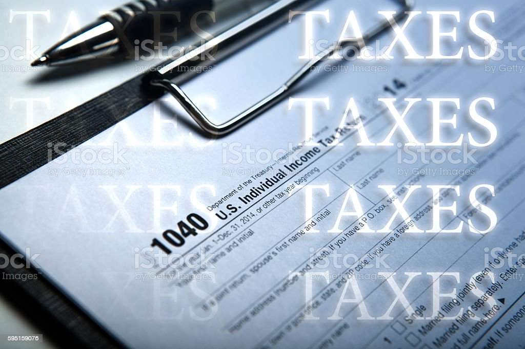 filling tax form on desktop with inscriptions taxes stock photo