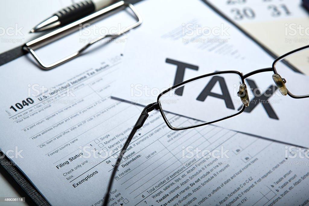 filling tax return on desktop stock photo