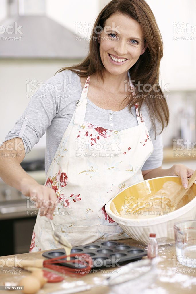 Filling the baking tray with her perfect cake mix royalty-free stock photo