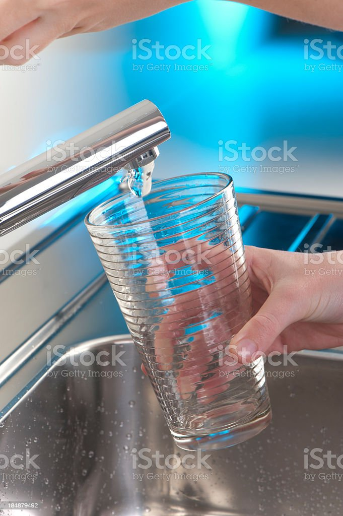 Filling up a glass of water in the kitchen sink royalty-free stock photo