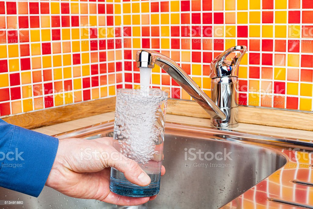 Filling up a glass with water from kitchen tap POV stock photo