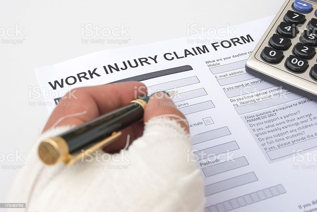 filling up a work injury claim form stock photo