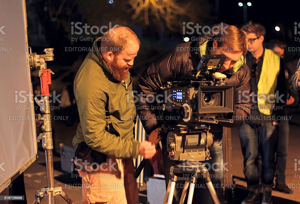 Film crew on location, night shoot. Cinamatographer with 4k camera stock photo