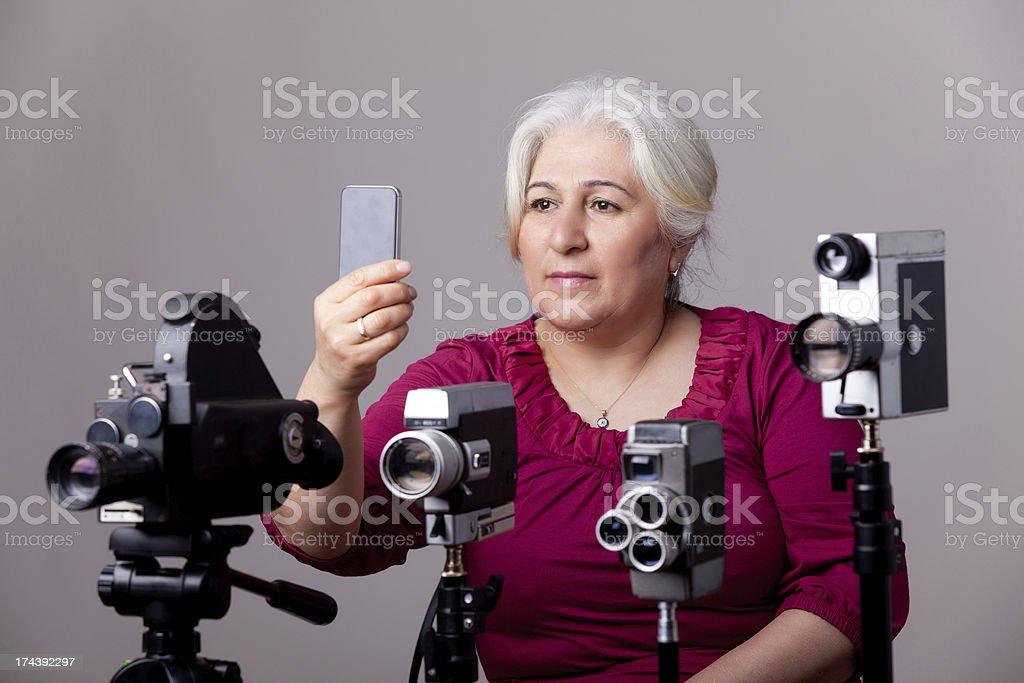 Film director behind camera shooting via mobile phone stock photo