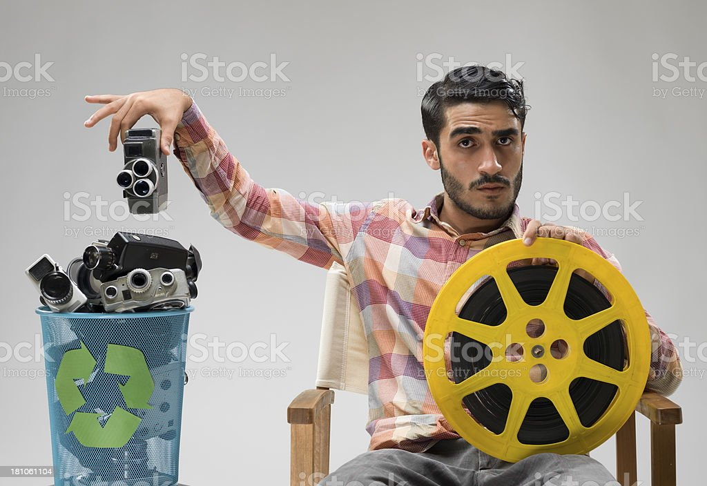 Film director casting away his camera to the garbage bin royalty-free stock photo