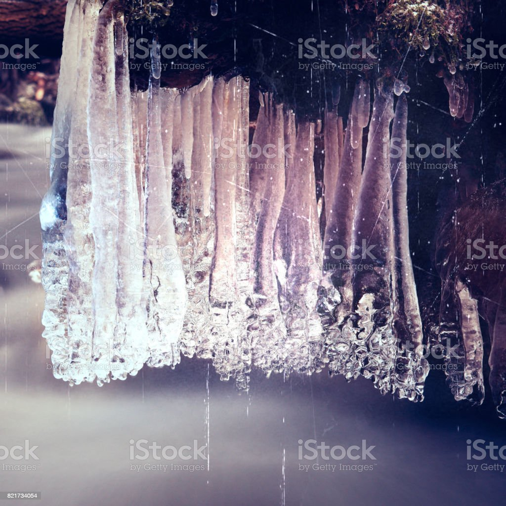 Film effect. Winter creek  with icicles above freeze  mountain stream. Winter season at river, shinning icicles stock photo