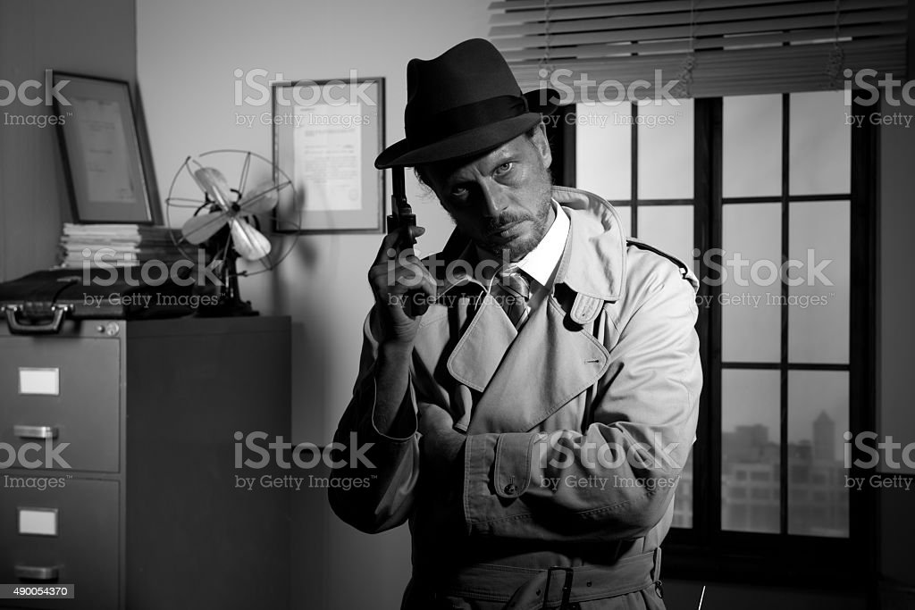 Film noir: detective holding a revolver and posing stock photo
