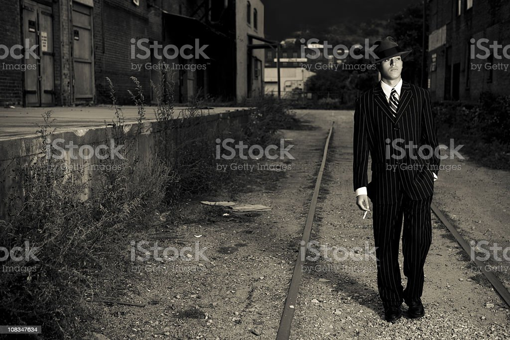 film noir style gangster walking in an alley stock photo