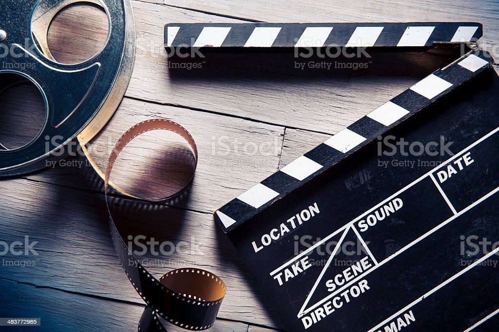 Film reel and movie clapper on wooden background stock photo