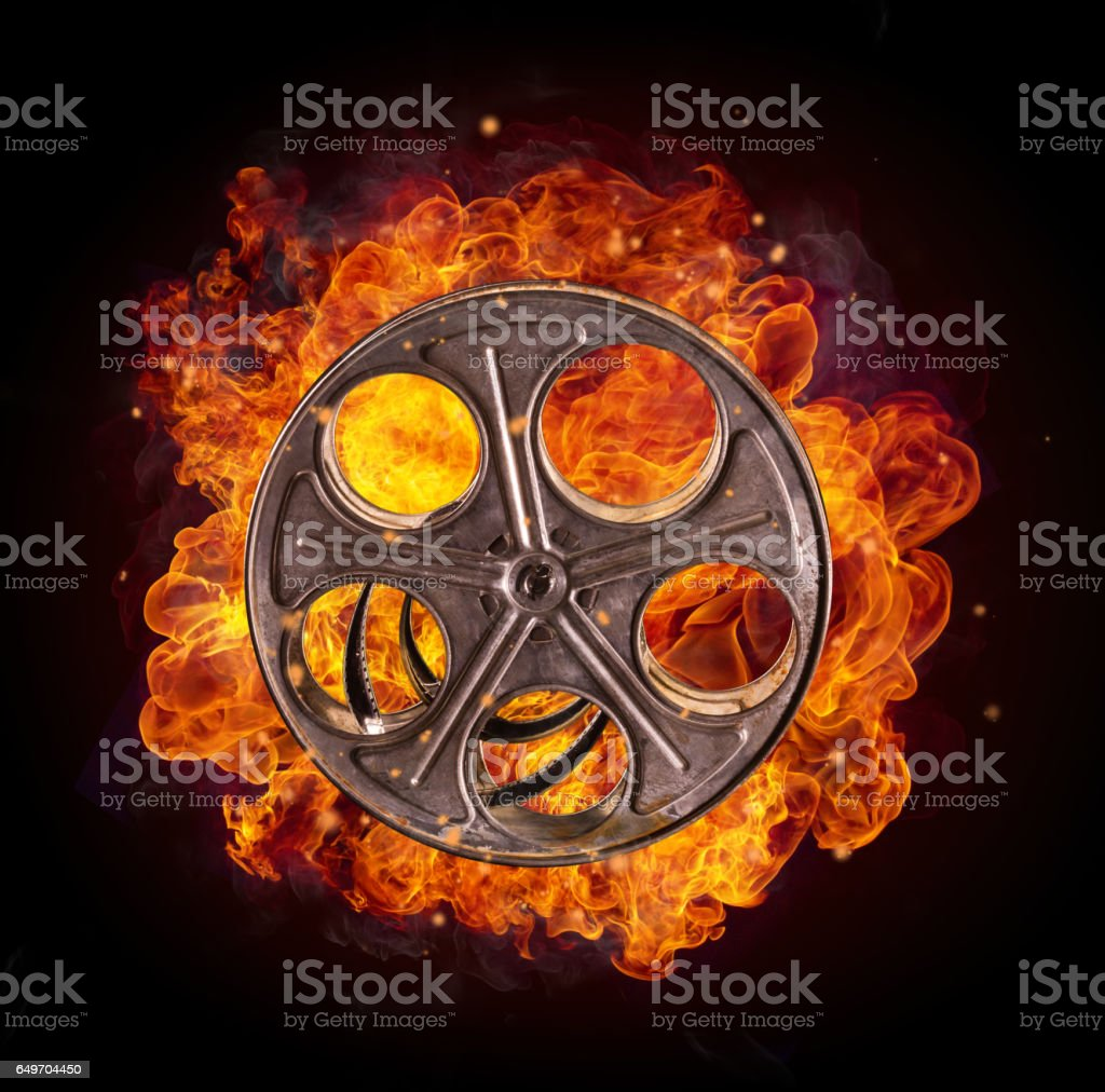Film reel in fire, isolated on black background stock photo