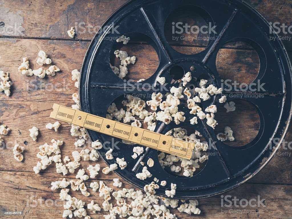 Film reel with popcorn and tickets stock photo
