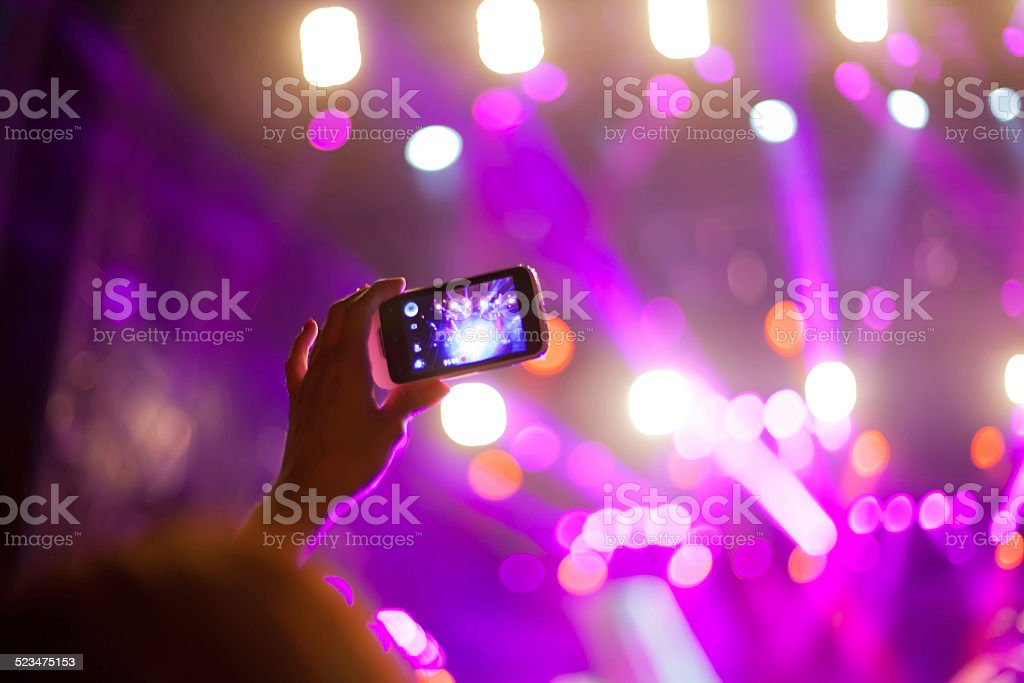 Filming with smart phone at concert stock photo