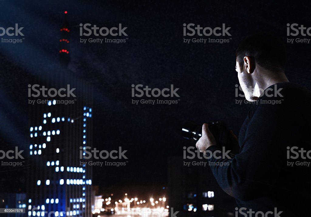 Filtered high-iso Image of photographer looking for night city stock photo