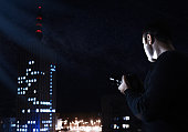 Filtered high-iso Image of photographer looking for night city