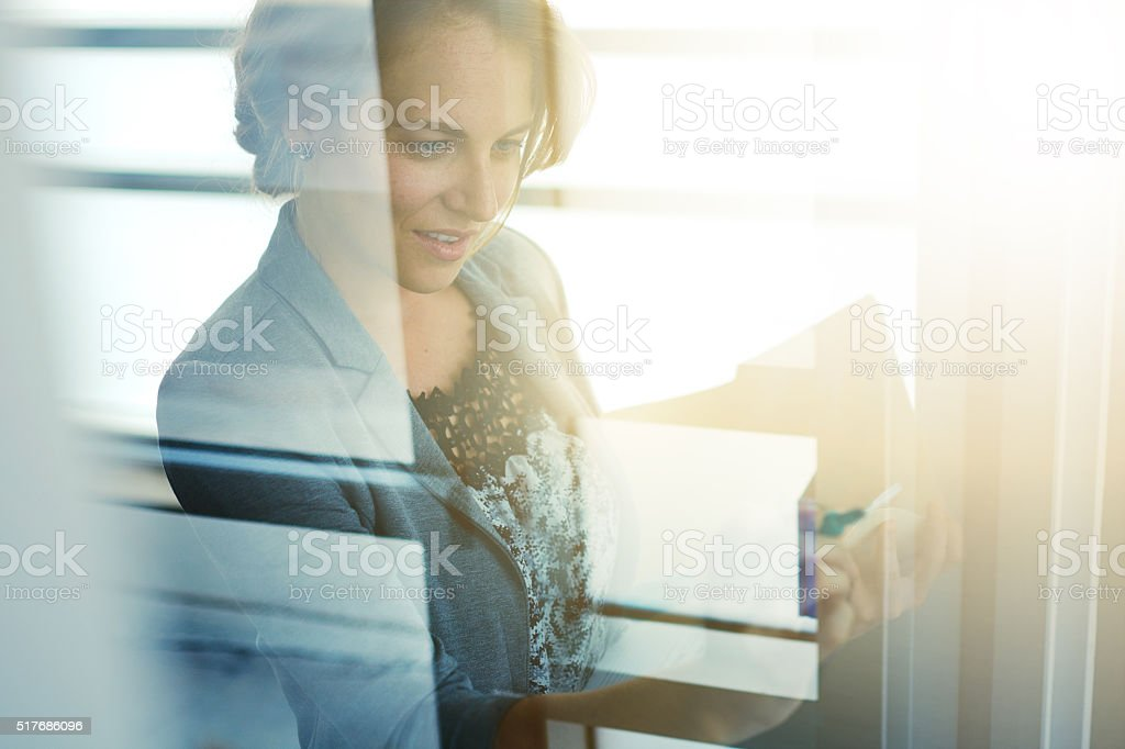 Filtered portrait of an executive business woman writing on a stock photo