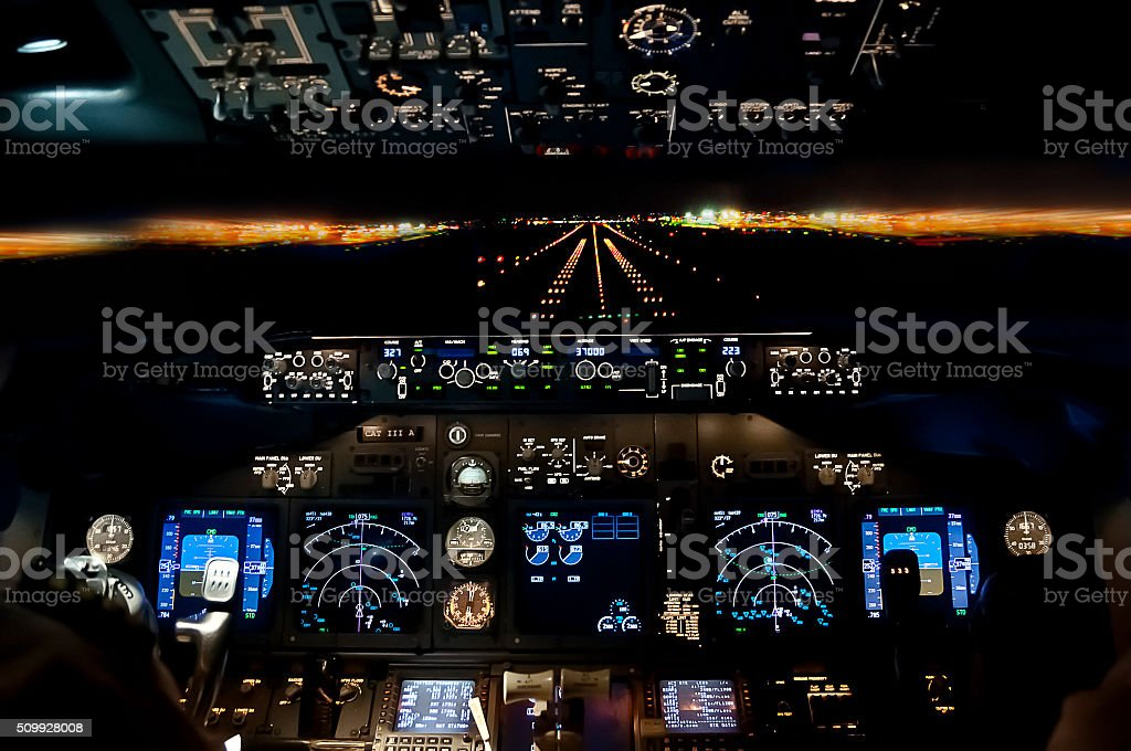 Final approach at night - landing plane flight deck view stock photo