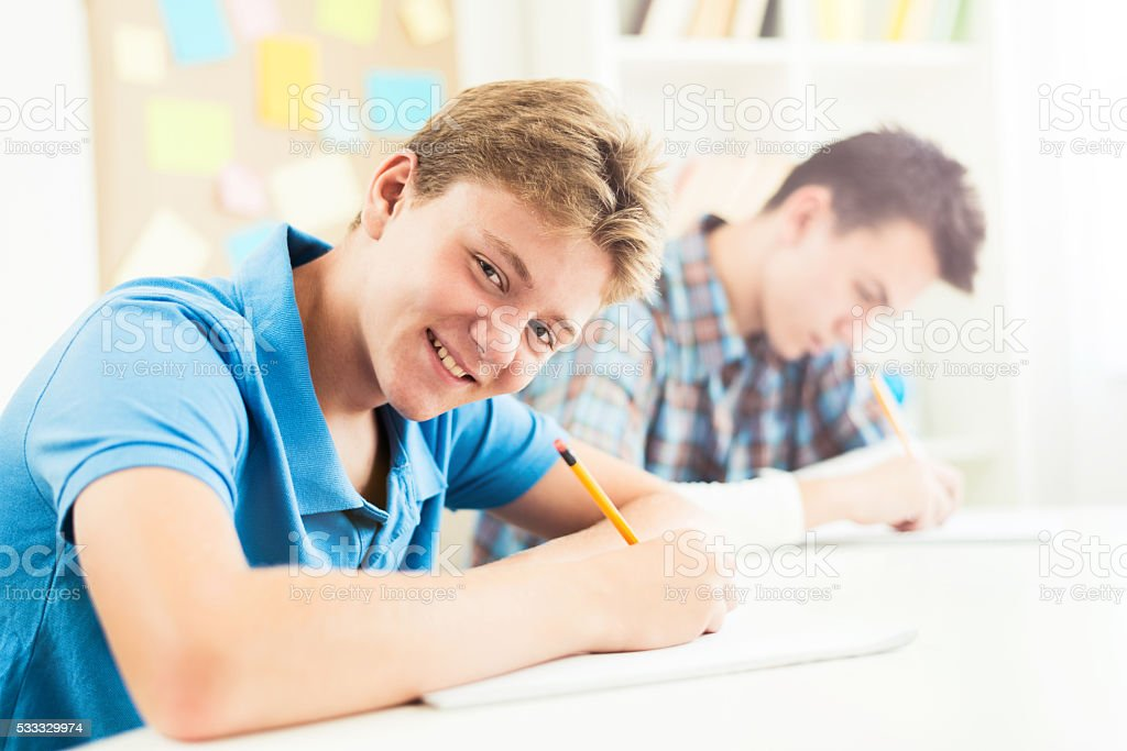 Two teenagers working on final exam