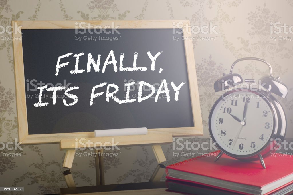 Final it's Friday on blackboard with flare and clock. stock photo