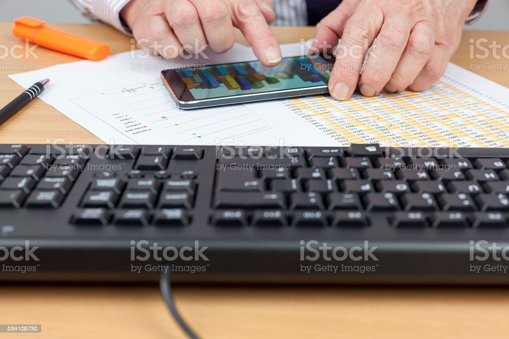 Finamcial account checking a chart on his smart phone stock photo