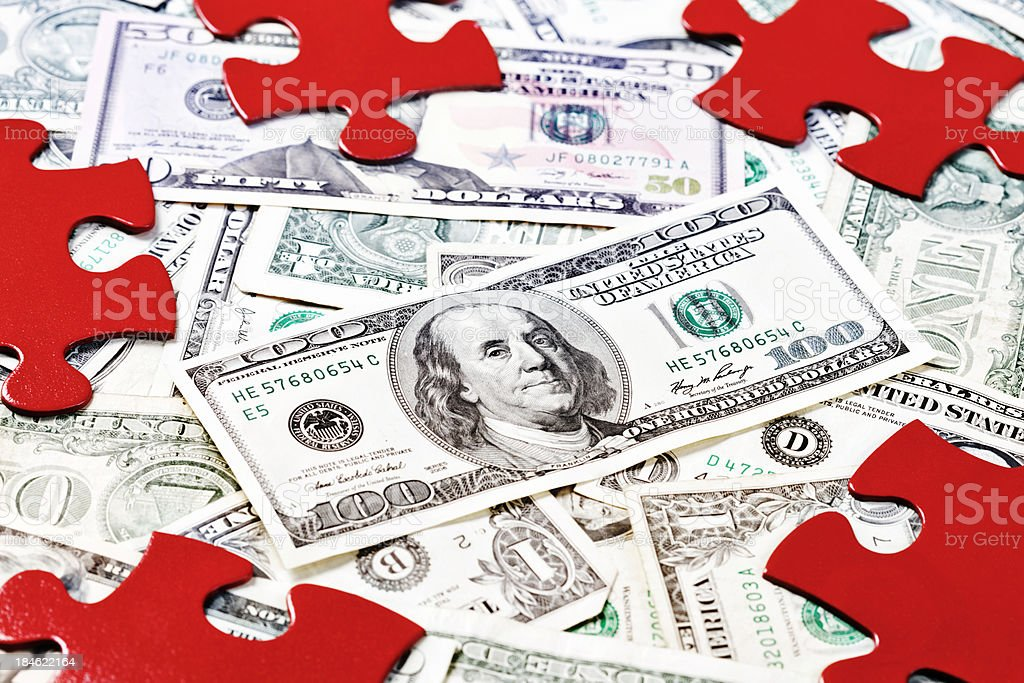 Finance can be puzzling: red jigsaw pieces on US dollars stock photo