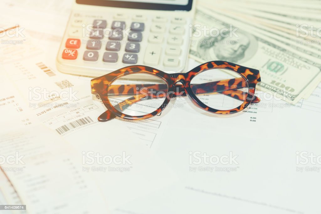 Finance concept : Eyeglasses , calculator and household bills stock photo