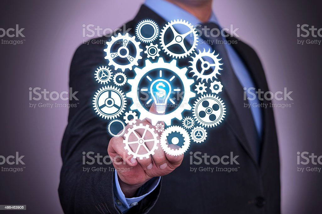 Finance Conceptual Idea Bulb and Gear Working on Touch Screen stock photo