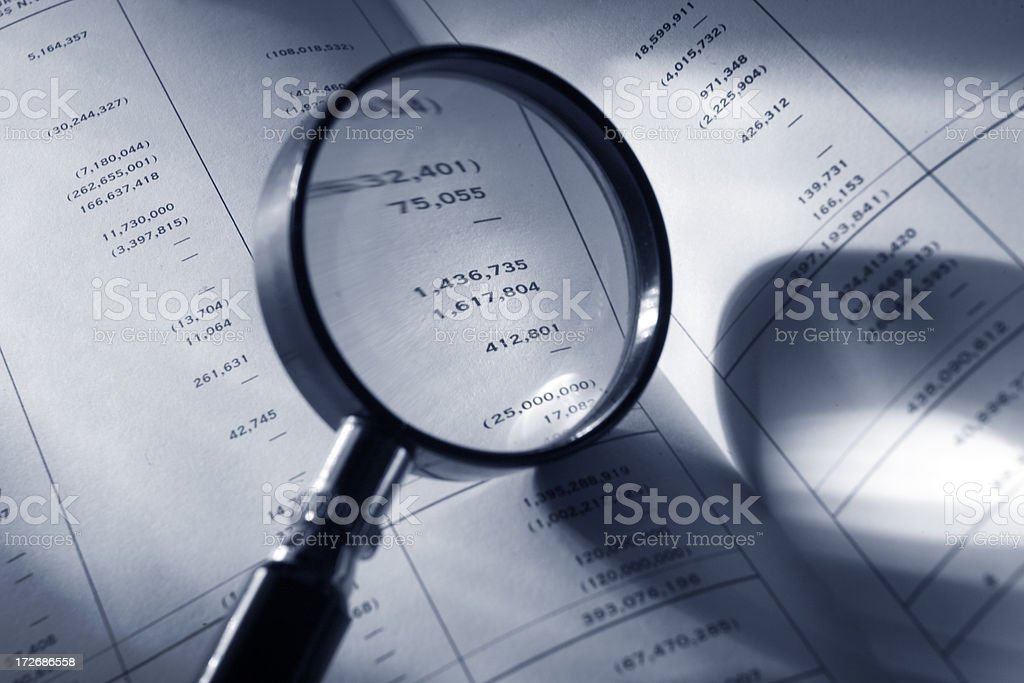 Finance: Magnifying Glass on Financial Report royalty-free stock photo