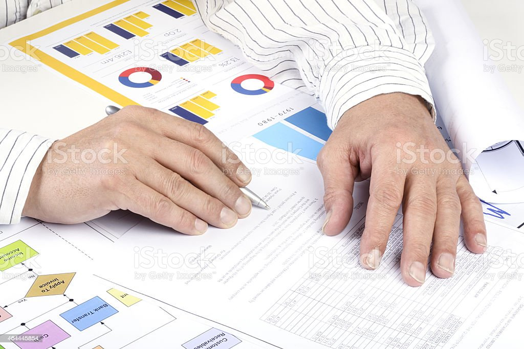 Financial adviser is reviewing report with charts and graphs stock photo