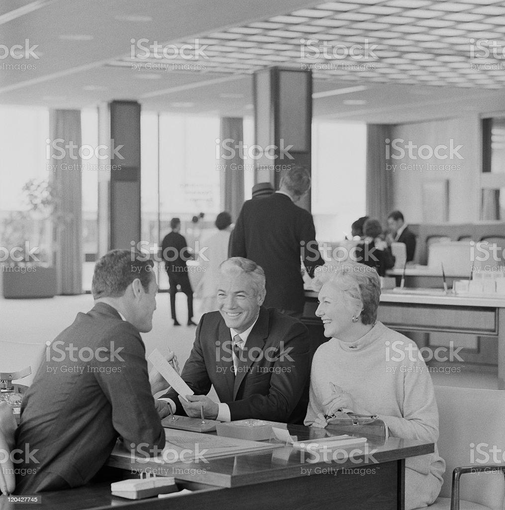 Financial adviser talking to couple, smiling stock photo