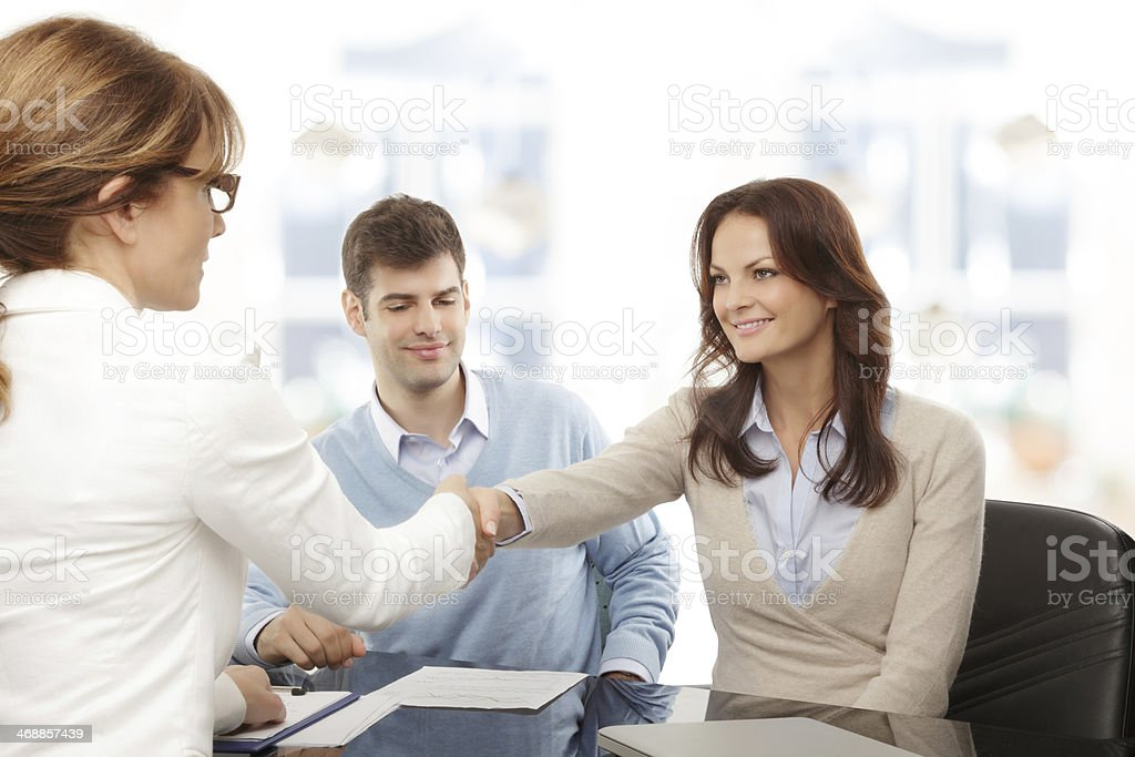 Financial advisor and client handshaking stock photo