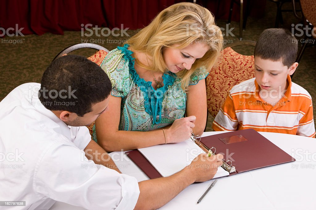 Financial advisor discussing college with mom and child stock photo