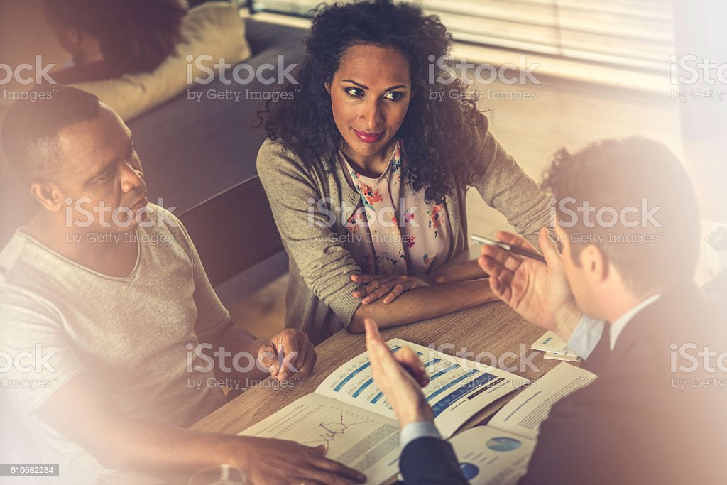 Financial advisor explaining savings plan to a couple stock photo